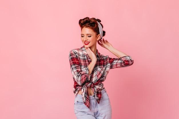 Гламурная женщина имбиря позирует на розовом пространстве. студия сняла мечтательную девушку кинозвезды в клетчатой рубашке.