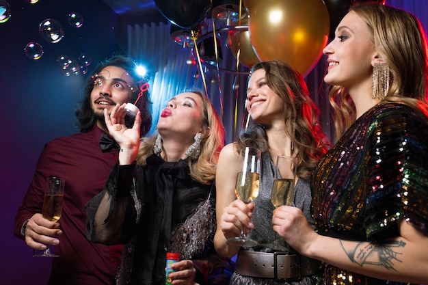 Glamorous girl blowing soap bubbles among friends with flutes of champagne at birthday party