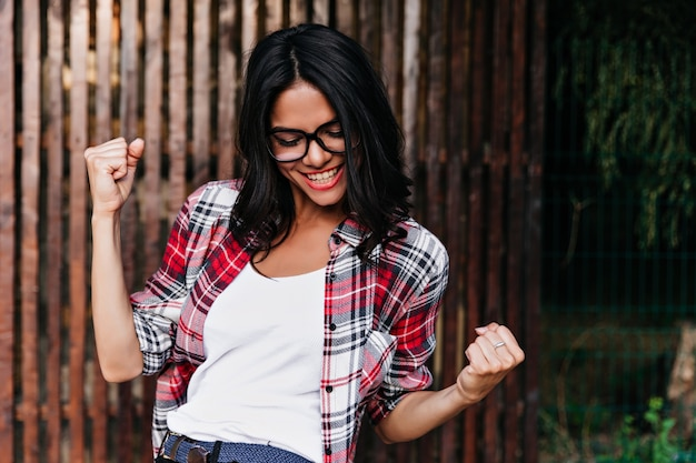 Glamorous girl in glasses having fun outdoor. ecstatic tanned woman in casual shirt expressing happiness on wooden wall.