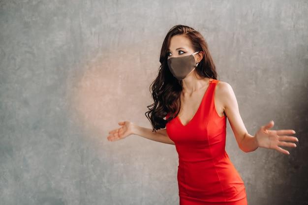 赤いドレスとヴィンテージの背景に保護マスクの魅力的な女の子