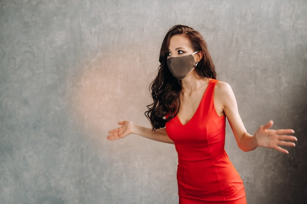 Glamorous girl in a red dress and a protective mask on a vintage background