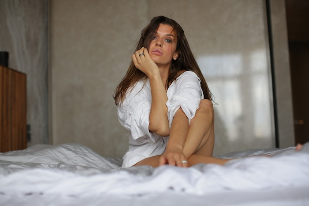 Glamorous girl sitting in a compact pose on white sheets.