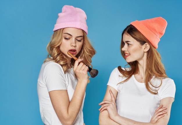 カラフルな帽子の化粧品の週末のライフスタイルのクローズアップで華やかなガールフレンド