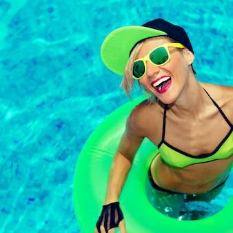 Гламурная счастливая девушка на жаркой летней вечеринке в бассейне