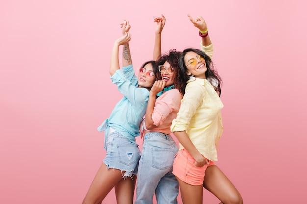友達と面白いダンスを楽しんでいる黄色いシャツを着た魅力的なヒスパニック系女性。身も凍るような3人の陽気な女の子の屋内ポートレート。