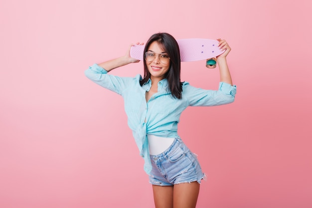 Affascinante giovane donna ispanica in abbigliamento alla moda in piedi in posa sicura e tenendo lo skateboard. incredibile ragazza dai capelli neri in pantaloncini di jeans e occhiali da sole alla moda in posa nella stanza blu.