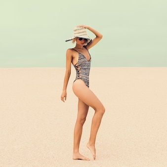 Glamorous lady in fashionable swimsuit and accessories at the beach on vacation