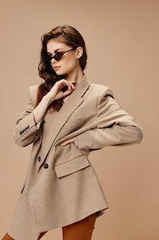 眼鏡とコートを着た華やかな女性が腰に手をかざす