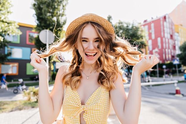 彼女の波状のブロンドの髪で遊んでいる魅力的な笑いの女性。黄色のドレスとヴィンテージの帽子の愛らしい女の子の屋外写真。