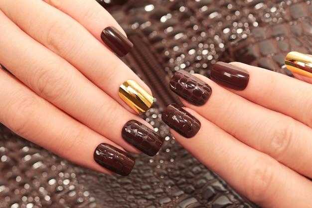 Гламурный роскошный коричневый маникюр из крокодиловой кожи с позолоченными женскими ногтями крупным планом