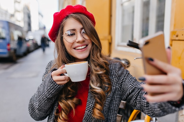 Affascinante ragazza pallida in bicchieri facendo selfie mentre beve il caffè nella caffetteria all'aperto