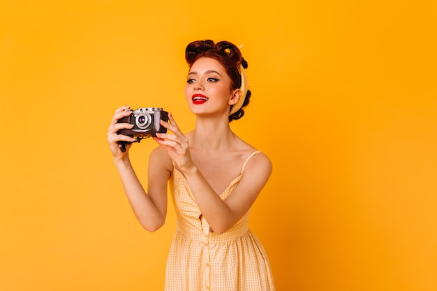 사진을 찍는 매력적인 핀 업 소녀. 노란색 공간에 카메라 서 영감 된 생강 여자.