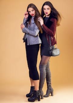 Donne graziose affascinanti che posano e indossano giacche invernali casual