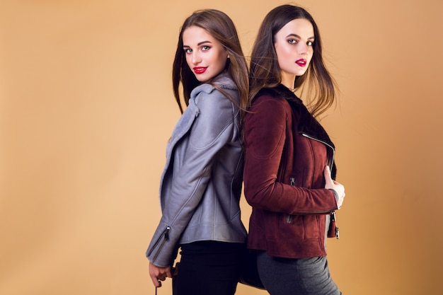 Donne graziose affascinanti che posano e indossano giacche invernali casual Foto Gratuite