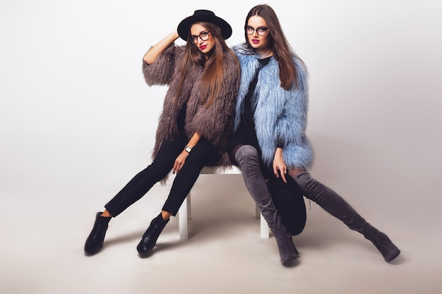 Glamorous pretty women posing and wearing fur coats