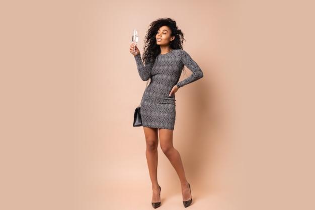 베이지 색 벽에 샴페인 잔을 들고 현대 반짝 드레스에 곱슬 헤어 스타일과 메이크업으로 매혹적인 매혹적인 여자. 파티 분위기. 전체 길이.