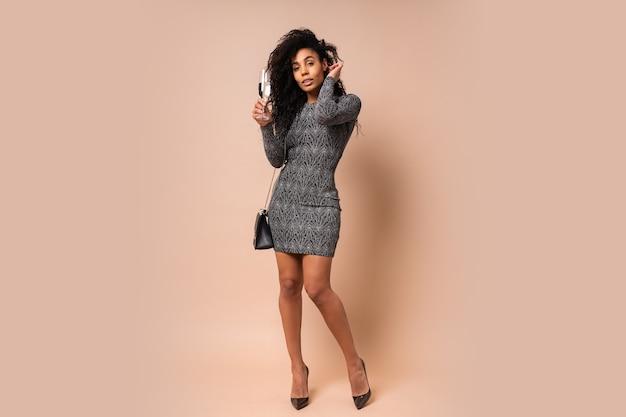 Гламурная сексуальная женщина с вьющейся прической и макияжем в современном блестящем платье держит бокал шампанского над бежевой стеной. праздничное настроение. полная длина.