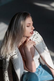 T- 셔츠에 세련된 청바지에 우아한 가죽 재킷에 매력적인 섹시 한 젊은 금발의 여자는 화창한 봄 날에 실내에 앉아