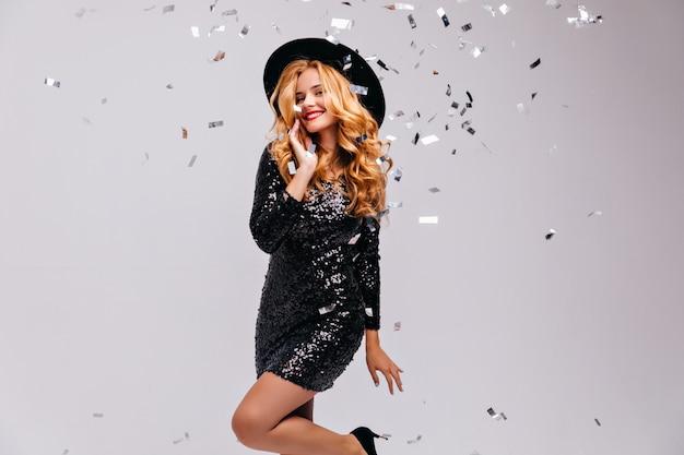 明るい壁にポーズをとって黒い帽子の華やかな笑顔の女の子。光沢のあるドレスを着た見事な巻き毛のブロンドの女性の屋内ショット。