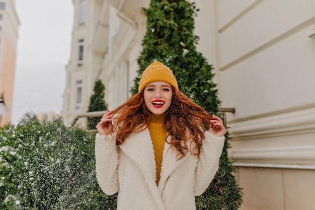 겨울 날에 그녀의 생강 머리를 가지고 노는 매력적인 웃는 소녀. 녹색 전나무 근처에 서있는 멋진 유럽 아가씨의 야외 사진.