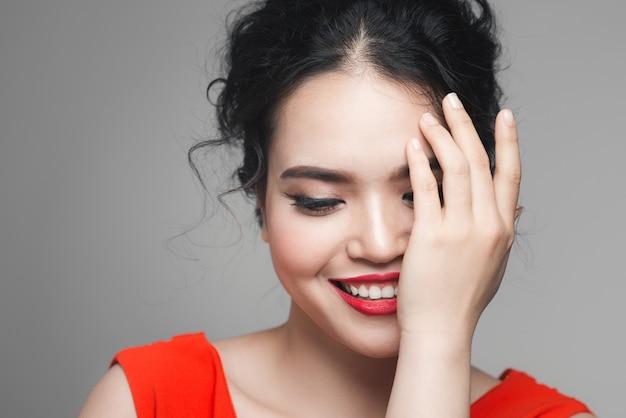 イブニングメイクの華やかなスタイリッシュな女性は、手のひらで顔の半分を覆っています