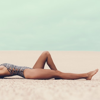 Glamorous tanned lady in a fashionable swimsuit and at the beach
