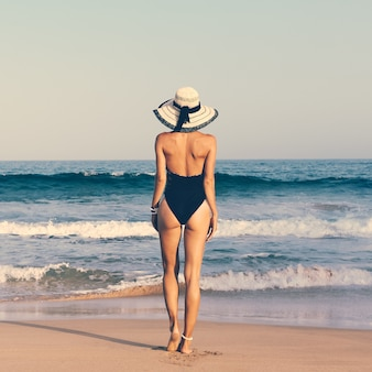 Glamorous tanned lady in fashionable swimsuit and hat on the beach