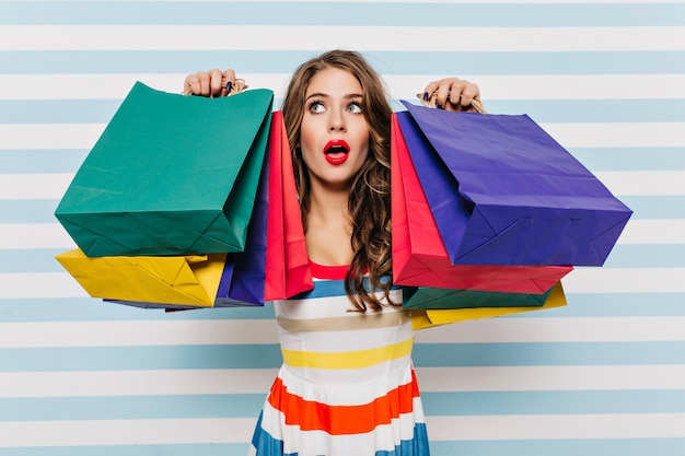Glamorous tired girl with red lips posing after shopping. indoor photo of dreamy female shopaholic wears striped colorful dress.