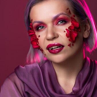 Гламурный образ вампира с ярко-розовыми тенями для век и лепестками цветов на коже.