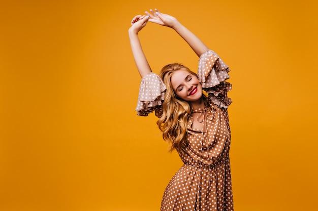 Гламурная белая женщина, протягиваясь с закрытыми глазами. интерьерное фото очаровательной позитивной девушки в коричневом платье.