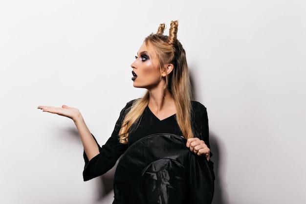 할로윈에 흰 벽에 포즈 매력적인 마녀입니다. 뱀파이어 의상에서 파티를 즐기는 심각한 젊은 아가씨.