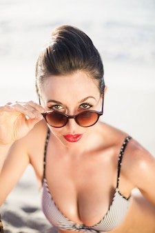 Glamorous woman in bikini looking over sunglasses