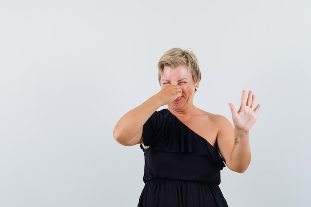 Glamorous woman in black blouse pinching her nose while raising hand up in rejecting manner and looking uncomfortable