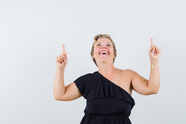 Glamorous woman in black blouse pointing up while laughing and looking cheery