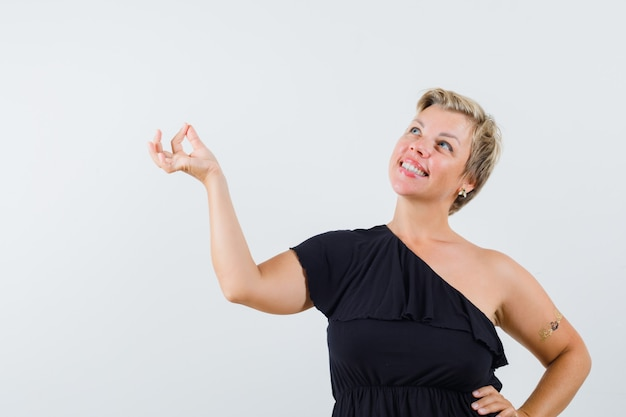 Glamorous woman in black blouse posing like pulling something down and looking positive
