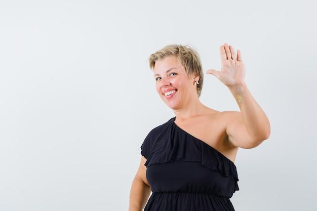 Donna affascinante in camicetta nera agitando la mano per il saluto e guardando allegra