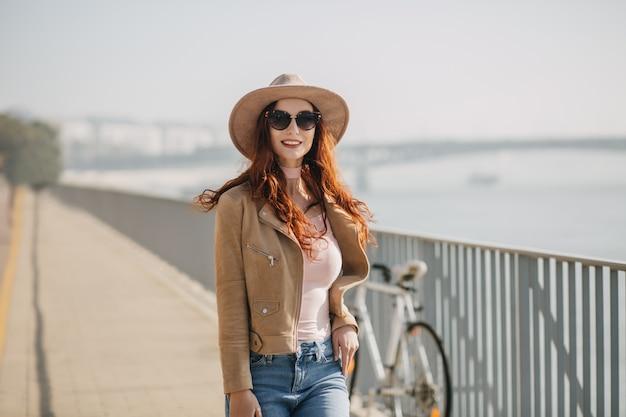 Donna affascinante in occhiali da sole neri in posa sul ponte con la bicicletta sul muro