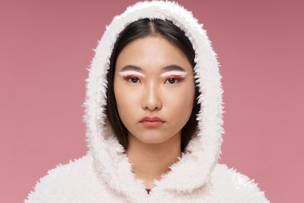 華やかな女性の明るいメイク冬ジャケットピンク背景