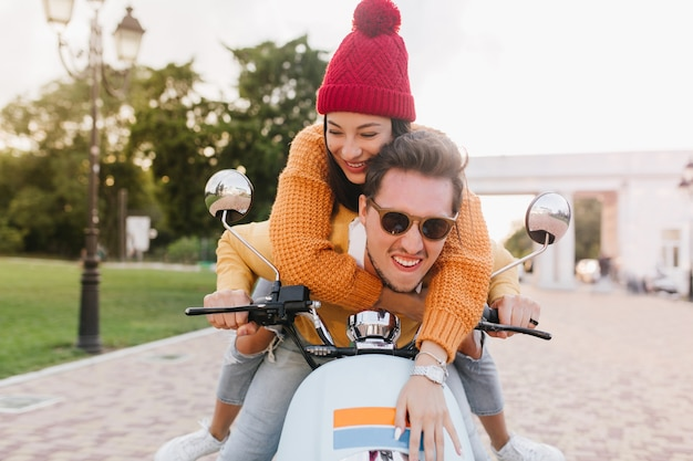Glamorous woman in cute knitted hat looking away with smile, riding on scooter with boyfriend