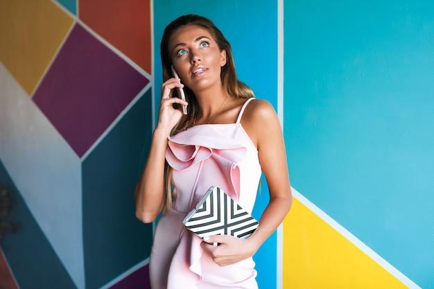 Donna affascinante in vestito rosa elegante che comunica dal telefono
