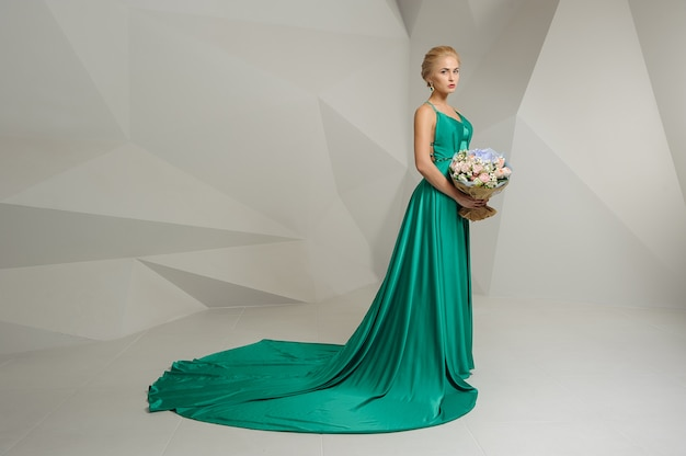 Glamorous woman in a green dress with blond hair holds a bouquet
