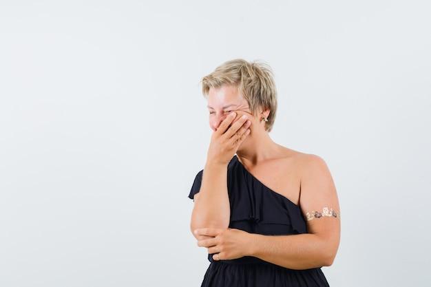 Donna affascinante che tiene la mano sulla bocca in camicetta nera e sembra allegra. vista frontale. spazio per il testo