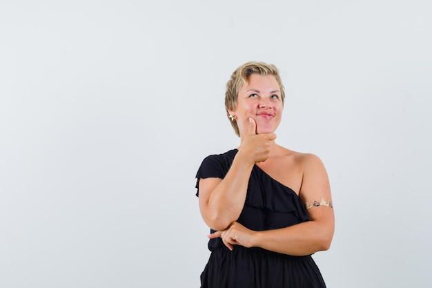 黒のブラウスで見上げて自信を持って見ながら顎に手をつないでいる華やかな女性。正面図。テキスト用のスペース