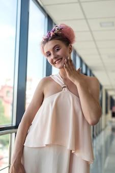 ファッションメイクで壁にベージュの服を着た華やかな女性