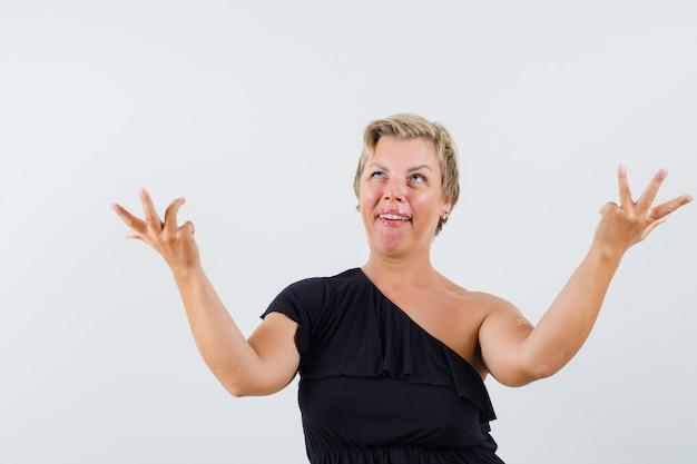 疑わしい方法で手を上げる黒いブラウスの魅力的な女性