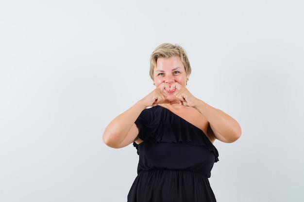 Гламурная женщина в черной блузке показывает жест мира и выглядит любимой