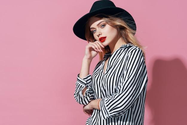 黒い帽子とストライプのシャツの明るい化粧ピンクの背景の魅力的な女性