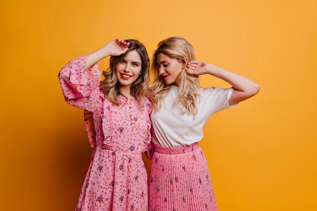 妹と余暇を過ごすかわいいピンクのドレスを着た華やかな女性。ポジティブな感情を表現する素晴らしい女性モデルの屋内写真。
