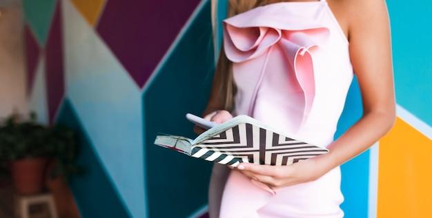 ノートブックとスマートフォンを保持しているエレガントなピンクのドレスの魅力的な女性