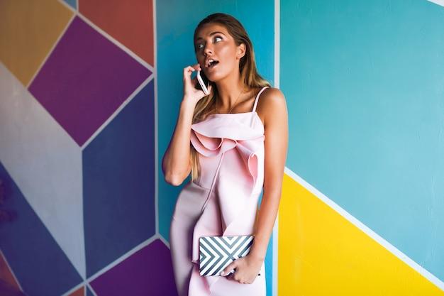 電話で話しているエレガントなピンクのドレスの魅力的な女性